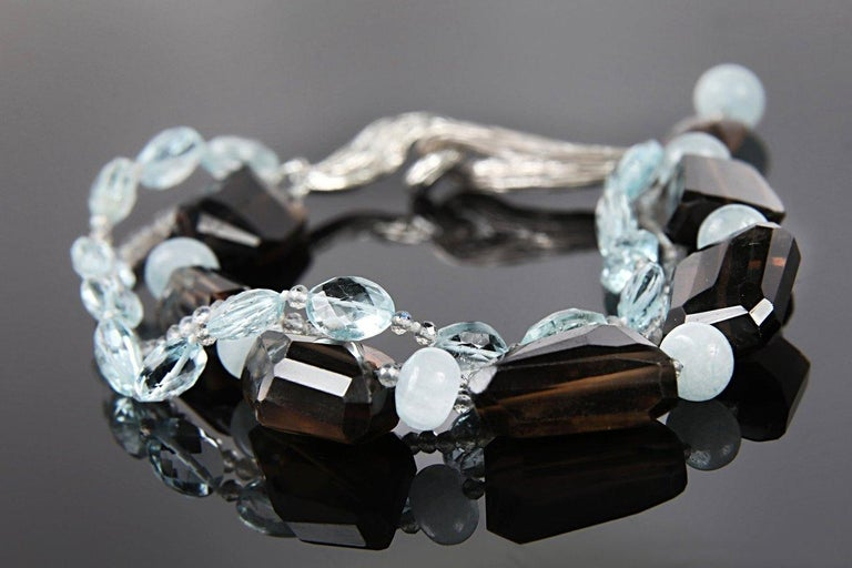 A three-strand bracelet of two shapes and colors of aqua, smoky quartz chunks (20 mm), and microfaceted labradorite. The bracelet is finished with a hypersthene and aqua tassel on a handcrafted White Orchid Studio vanilla bean clasp.