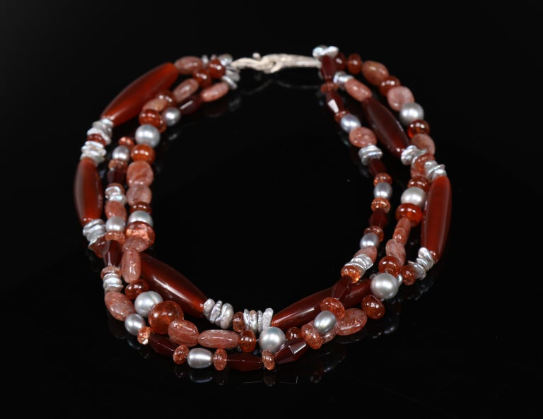 A three-strand necklace of dark carnelian, sunstone, and silver freshwater pearls. The necklace is finished with our artisan-crafted vanilla bean clasp in 925 sterling.  18