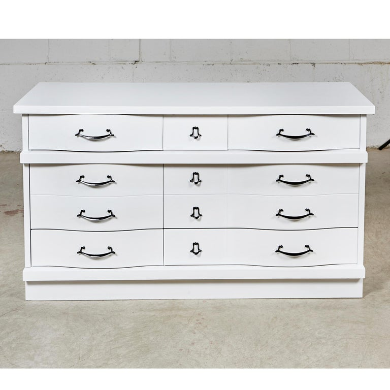 Vintage 1960s white painted three-drawer dresser with black painted pulls. Middle drawer is doubled in size. Newly refinished condition.