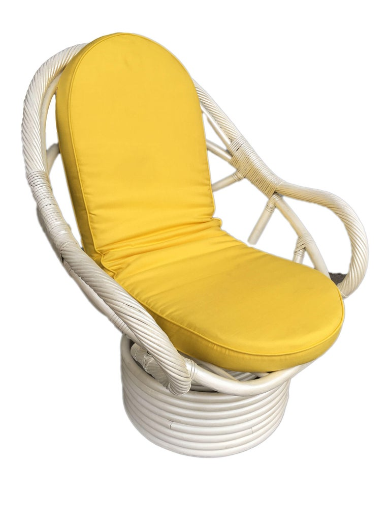 White painted rattan bucket lounge chair with swivel base featuring a ball-like shape with stick rattan wrapped arms. Circa 1970 Cushions are C.O.M. Restored to new for you. Restored to new for you. All rattan, bamboo and wicker furniture has been