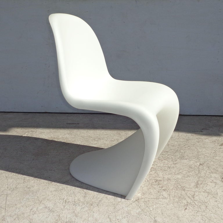 White Panton chair by Verner Panton for Vitra with Side Stool  Captivated by the potential of plastic, Danish designer Verner Panton created the first single-form injection-molded chair, which was originally manufactured by Vitra for Herman Miller