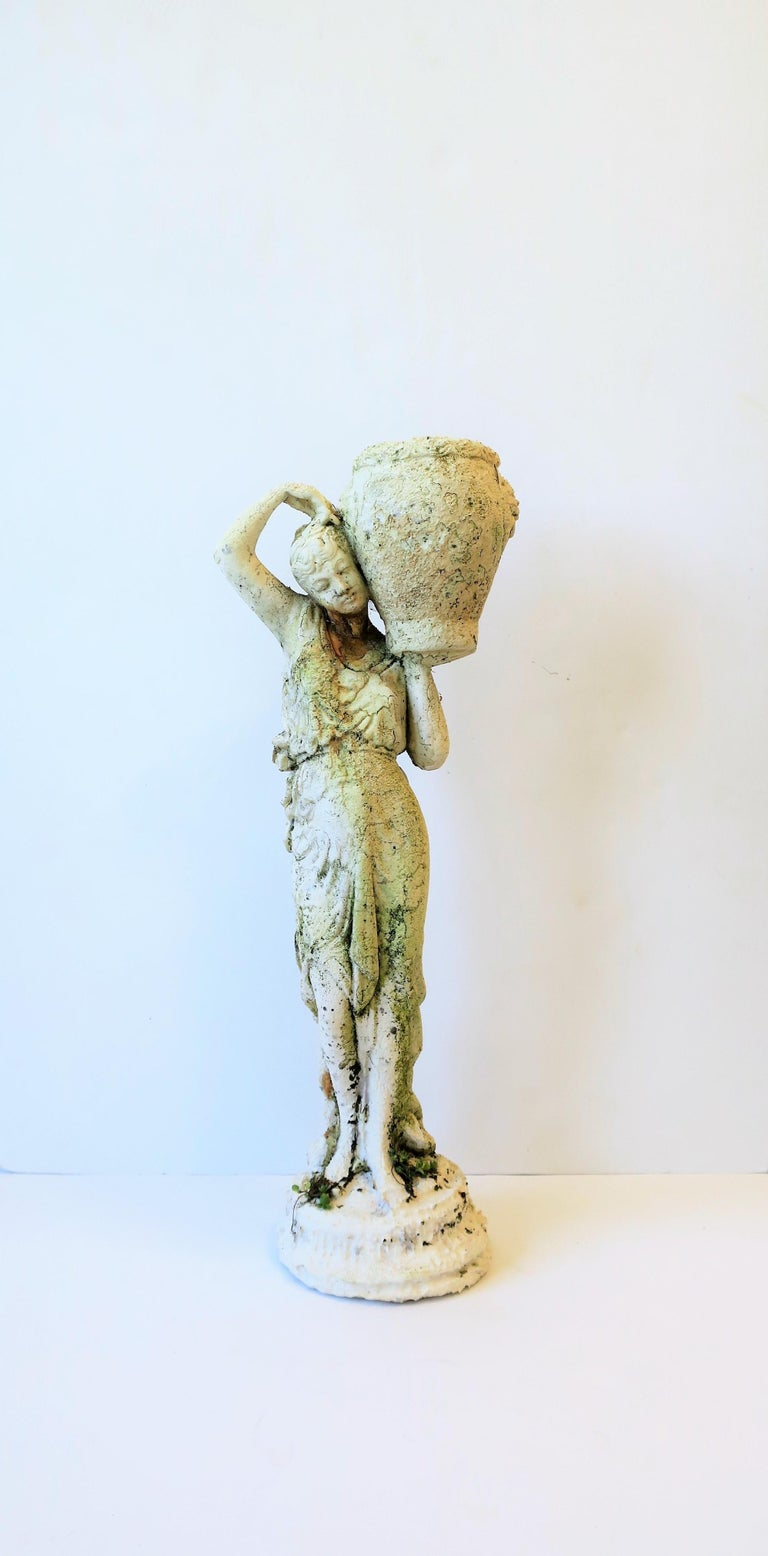 A beautiful white plaster and cement combination Female garden sculpture piece with decorative pot, circa Mid-20th Century, Italy. Sculpture has beautiful details; she looks great from the front and the back as show in images. She holds a pot on her