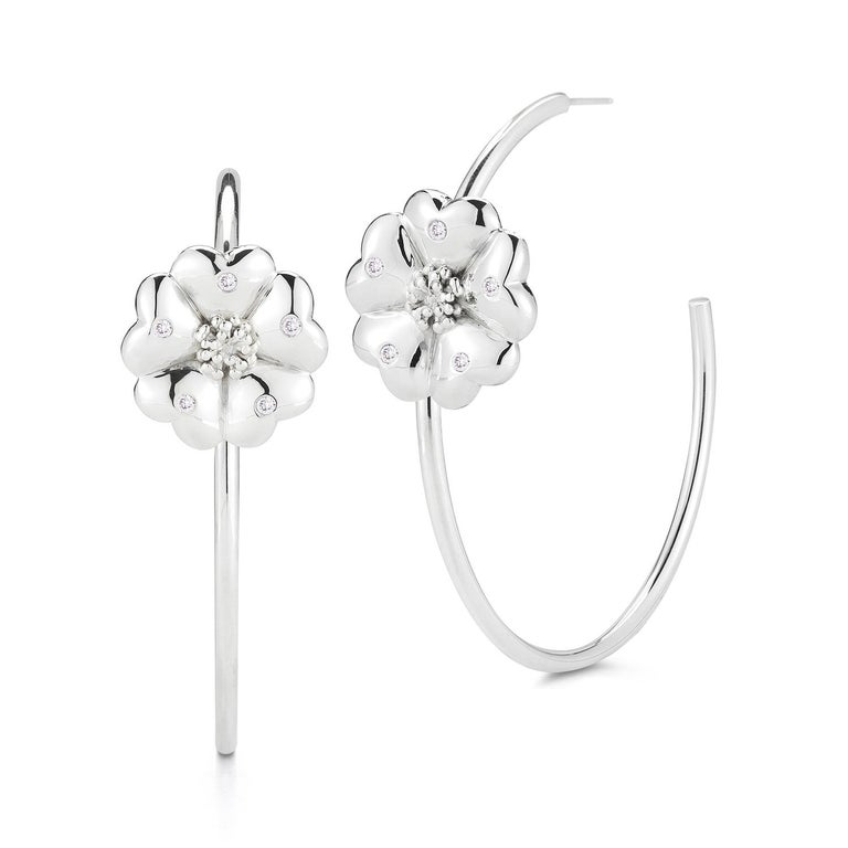 Designed in NYC  .925 Sterling Silver White Sapphire Blossom Pave Open Hoops. Beautiful blossom is front and center on this large statement open hoop. Blossom pave open hoops:       Sterling silver      High-polish finish     Medium-weight     20 mm