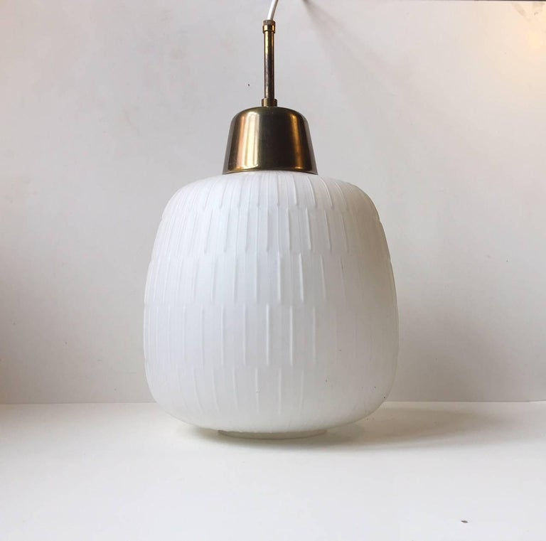 Large gourd shaped hanging light composed of fluted or reeded matte opaline glass with brass mount and tube. Manufactured and designed in Scandinavia most likely by either Fog & Mørup or Luxus. It remains in a nice vintage condition with only one