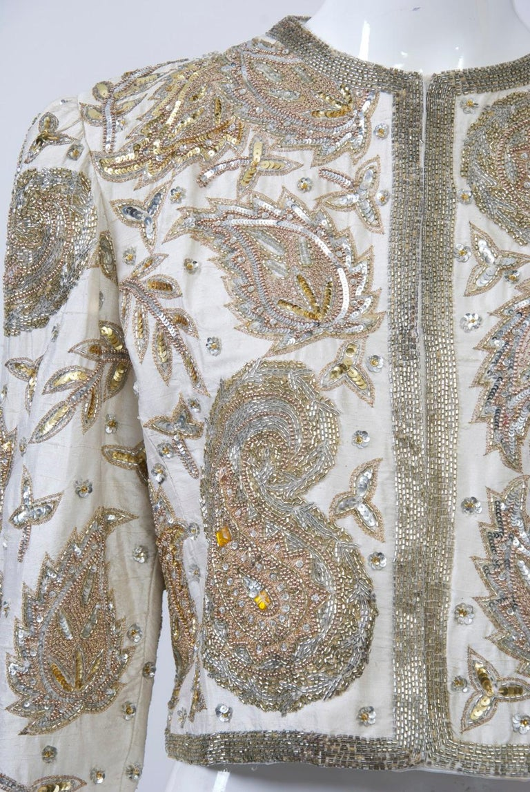 Bergdorf Goodman cropped evening jacket, the body of white silk heavily beaded in a paisley pattern with a variety of silver and gold beads and sequins punctuated with yellow and clear crystals at center. Set-in sleeves, collarless style ending at