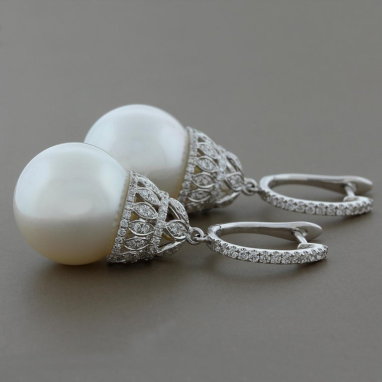 These elegant and feminine drop earrings feature two lustrous 16 mm South Sea pearls hanging from a royal design diamond and 18K white gold basket drop.  A total of 1.00 carat of VS quality diamonds are used.   Earring Length: 1 5/8 inches