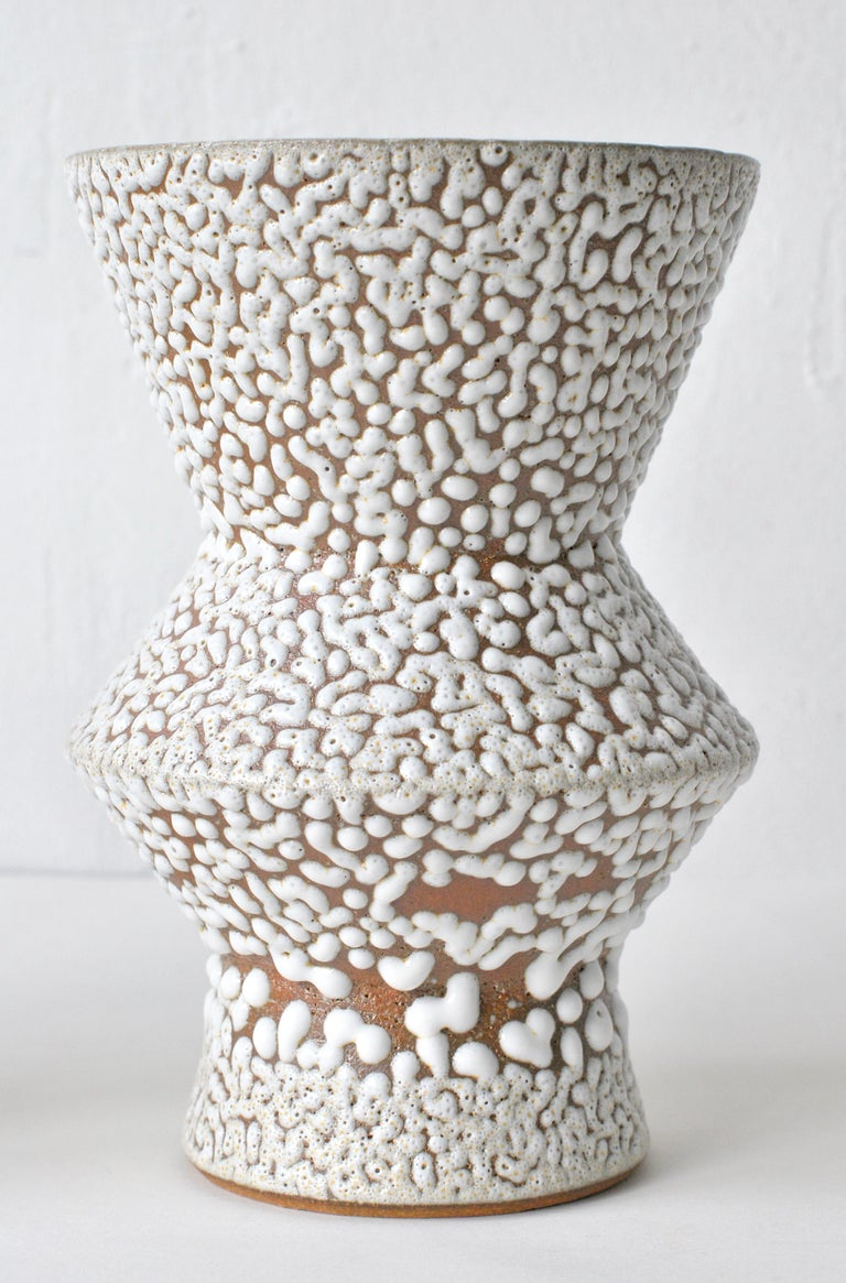 White stoneware vase by Moïo Studio Dimensions: 17 x 9 x 9 cm Materials: White crawl glaze on tan stoneware  Is the Berlin-based ceramic art studio of French-Palestinian artist Maia Beyrouti. It was created in 2016 as a result of the desire to