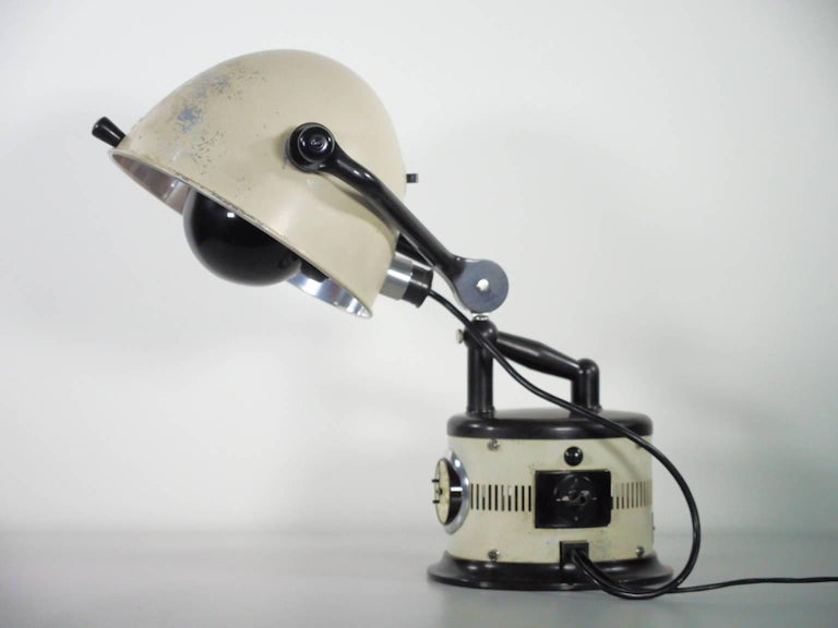 Rare vintage German sunlamp converted into a table lamp. White lacquered metal and black metal details. Adjustable light point. Wear consistent with age and use.