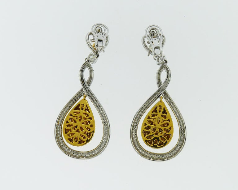 Beautiful drop earrings made in the shape of a tear. The center part is embellished with yellow diamonds framed with a halo encrusted with white round diamonds. Total weight of diamonds is approximately 11.00 carats. White diamonds are equivalent to