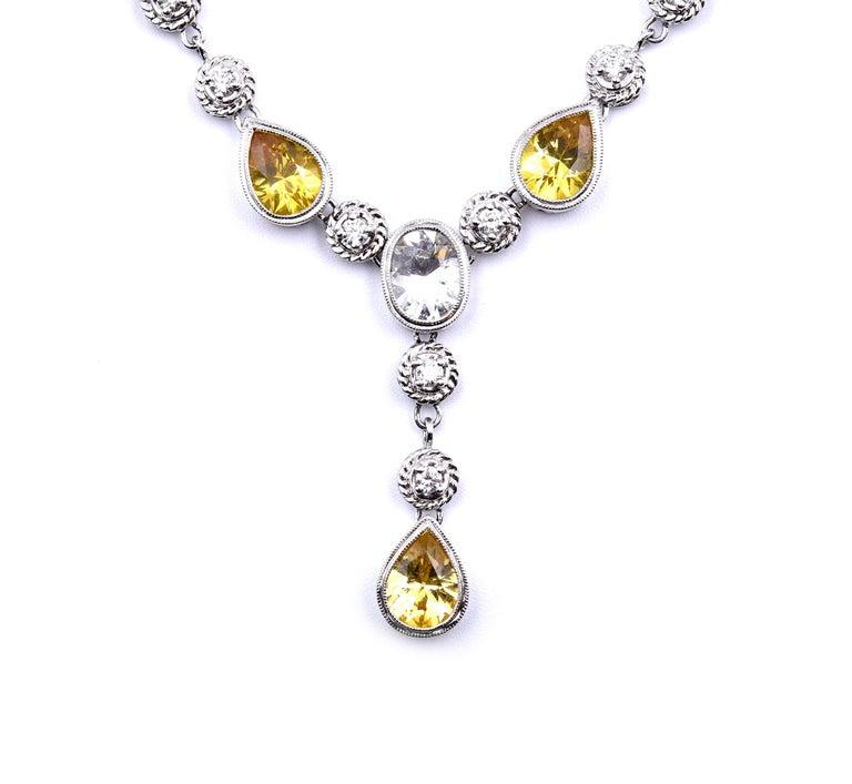 Designer: custom design Material: 18k white gold Yellow Sapphires: nine pear cut sapphires = 11.14 carat weight White Sapphires: 1.34 carat white sapphire Diamonds: 18 round brilliant cut diamonds = 0.79 carat weight Color: G-H Clarity: