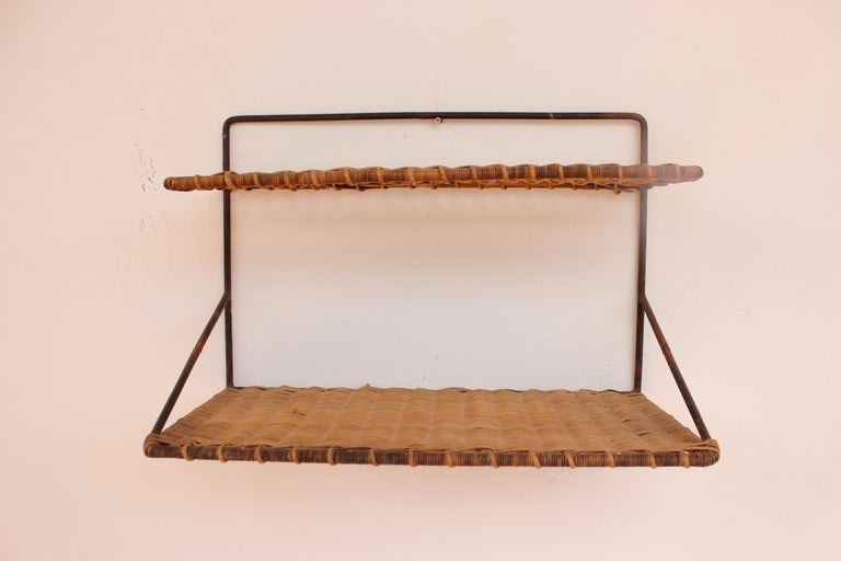 Wicker and black metal shelf by Raoul Guys, France, 1950.