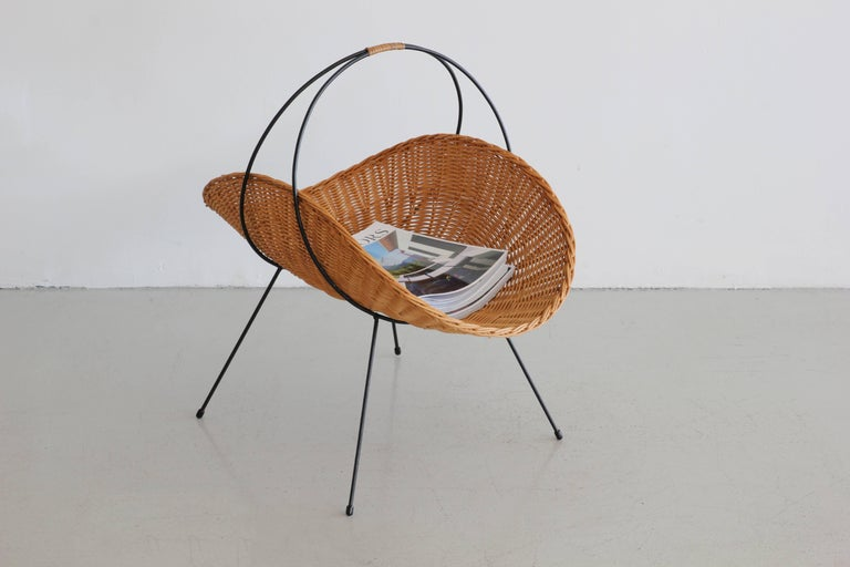 Large wicker magazine basket on slender iron legs and iron handle. Classic midcentury style.