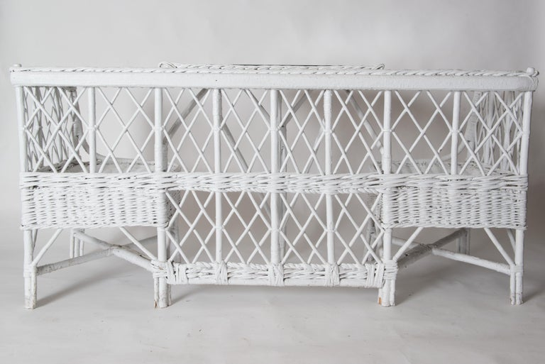 Very rare vintage wicker/reed banquette or booth. One wicker piece includes two corner chairs and an attached wicker table with a protective glass top. A very fun unique piece for a porch, a playroom, a pool house, anywhere you want a conversation