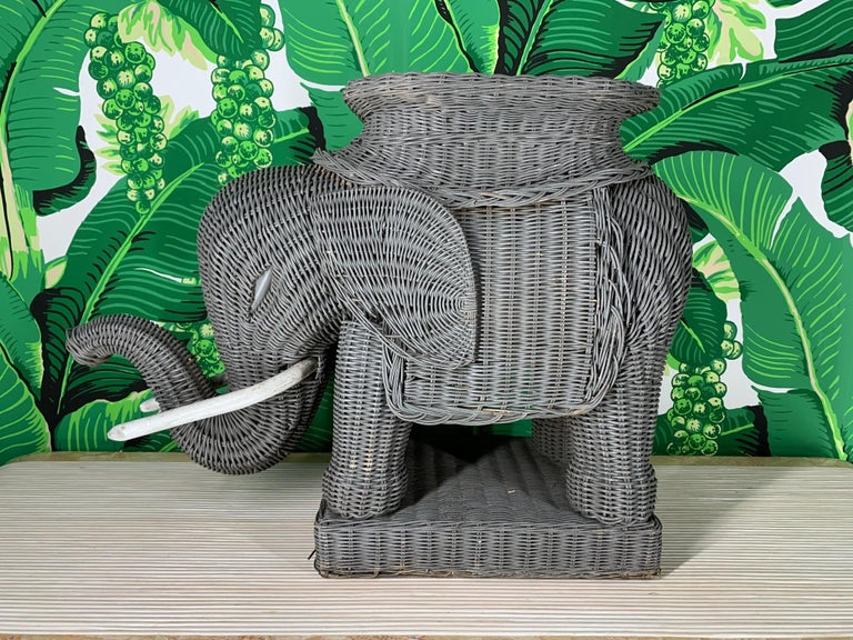 Vintage 1960s-1970s woven wicker elephant garden stool/side table in excellent condition. Rigid wood frame construction with densely woven sculpted wicker. Wooden tusks and plinth style base. Very good condition.