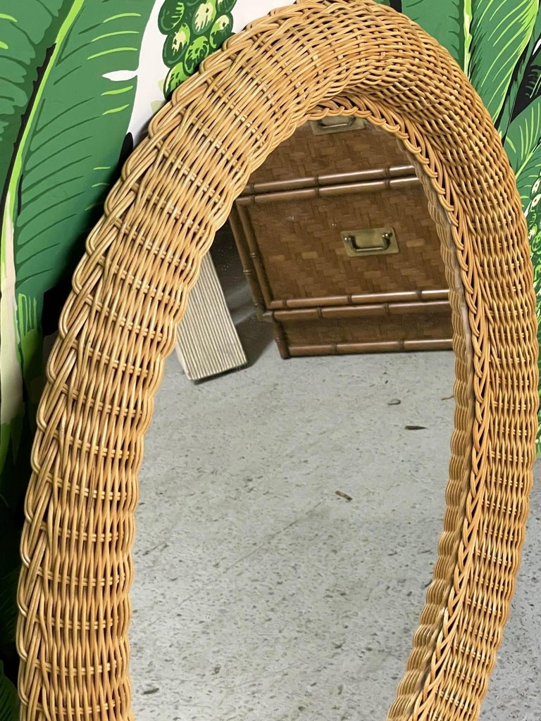 Oval wall mirror in natural wicker with braided accent. In the style of Bielecky Brothers. Very good condition with almost no imperfections.
