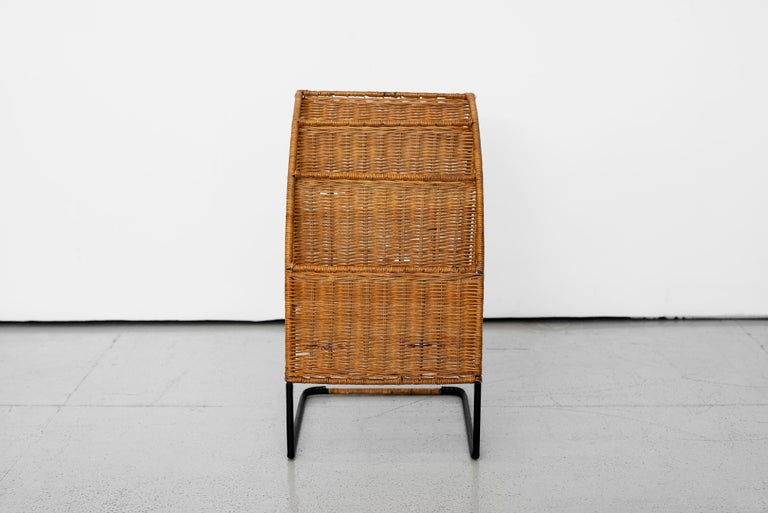 Unique French magazine rack attributed to Jacques Adnet. Multi-tier wicker rack with iron frame and newly wrapped black leather base.