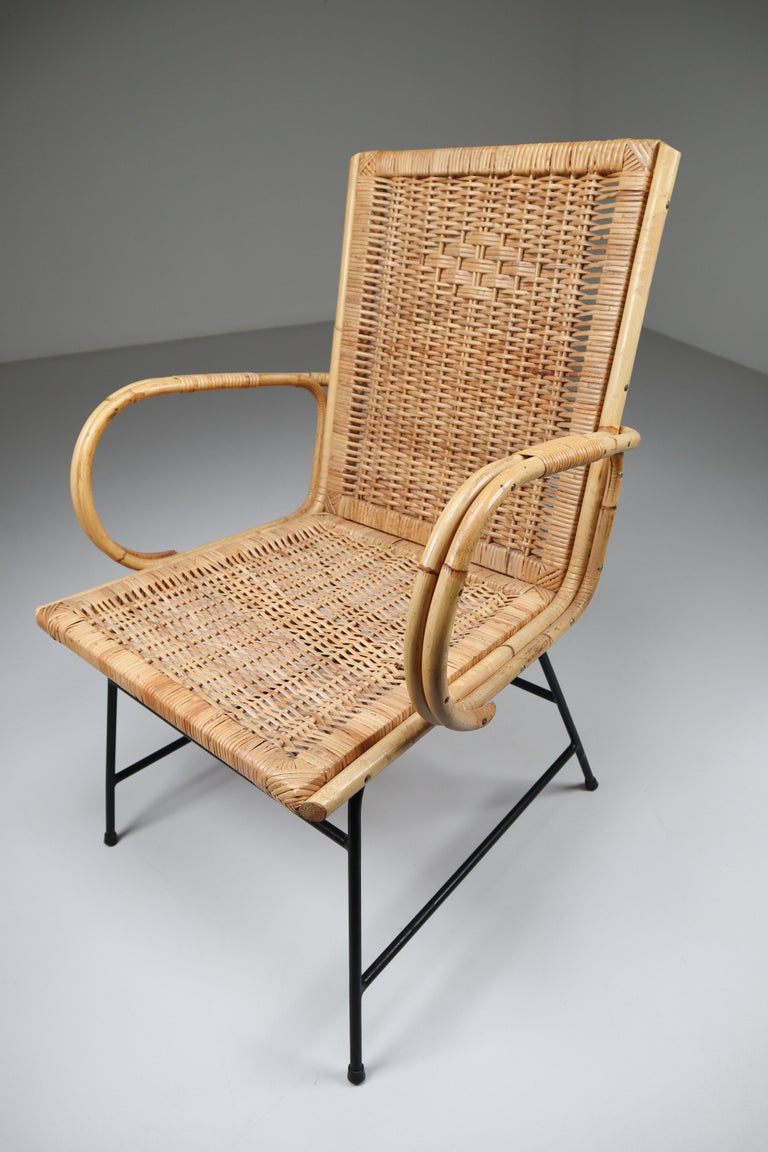 Wicker midcentury armchair designed and produced in France during the 1960s. The chair is made from handwoven wicker for the seat and he frame is made of black lacquered steel. They are comfortable to sit in and create an inviting sitting