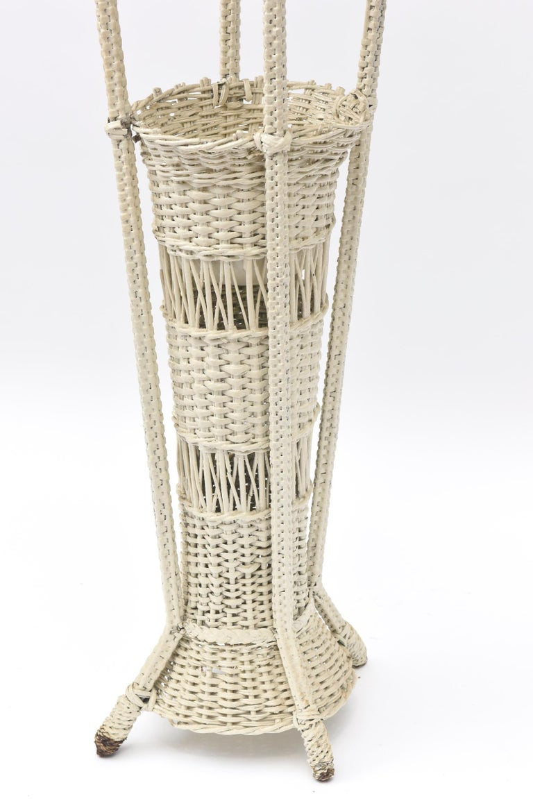 A rare example of early 20th century wicker woven floor lamps, this one has a base which is a large vase or even an umbrella stand. Both the wicker base and the wicker shade are openly woven. There is a metal insert for water should you insert
