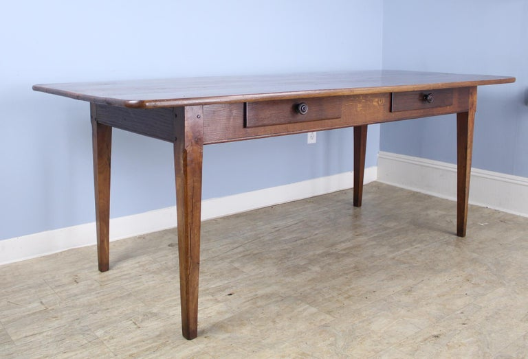 A two-drawer antique farm table with very good depth and wonderful dramatic walnut grain. Nice rounded corners on the tabletop add a modern note. Interesting carved detail at the top of the legs, which are 58.5 inches apart on the long side. 24-inch