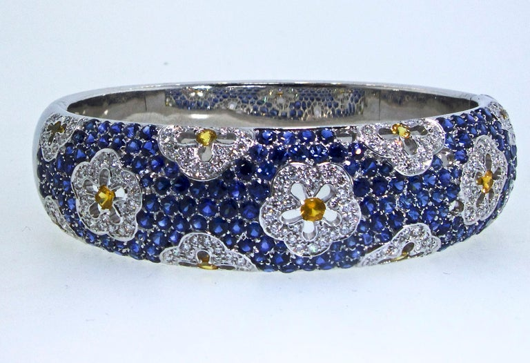 Sapphire and Diamond bracelet with floral motifs on a bed of blue sapphires.  This large 18K white gold bangle bracelet has sturdy, well made, clasp.  It is 7 inches in diameter.  The natural blue sapphires are bright and vivid, the natural yellow