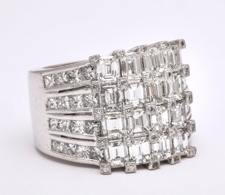 A FABULOUS PIECE!   7.18 carats of white Emerald cut and channel set Princess cut diamonds set in platinum.   Small white round brilliant cut diamonds cover each prong -- tons of sparkle in a unique design!  Currently a size 7.5, this ring is