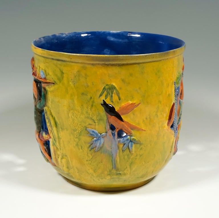 Cylindrical flower pot with breakthrough and relief-like shape of female figures carrying fruit bowls on their heads and plants with birds, painted in bright colors.  Manufactory: 'Wiener Werkstätte' /- 'Vienna Workshop' Dating: made