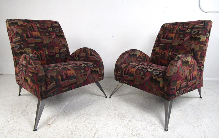 This beautiful pair of Italian modern lounge chairs boast unusual splayed metal legs and unique ellipse-shaped armrests. A wild Art Deco/midcentury style design that ensures maximum comfort in any setting. The extremely soft fabric has wonderful