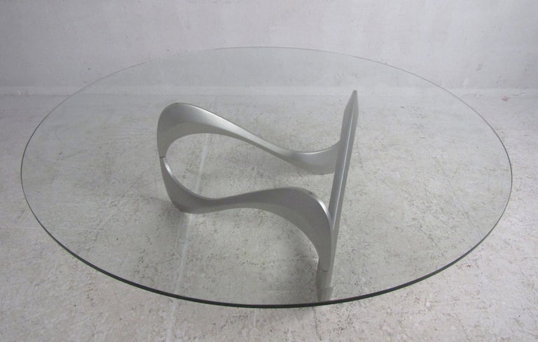 This amazing vintage modern coffee table boasts a thick circular glass top with beveled edges. Sleek design with a scribble shaped, sculped metal base. This lovely table makes the perfect addition to any home, business, or office. Please confirm the