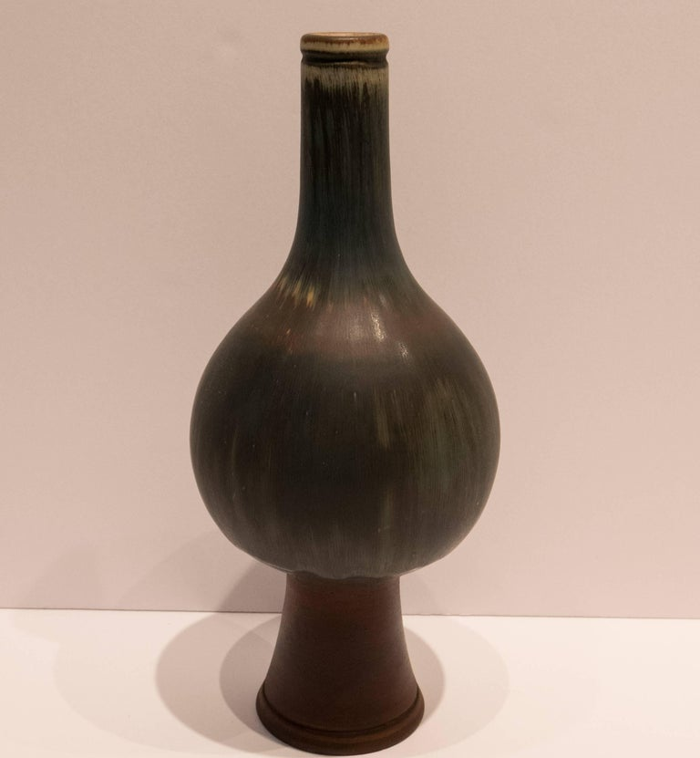 Exceptional vase with bulbous centre and long neck, with a subtle modulated multi-chromatic drip glaze and unglazed tapering foot. From Wilhelm Kage's Farsta series, essentially his studio work at Gustavsberg, produced, circa 1950. Full incised