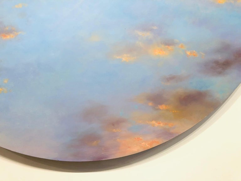 Luminous Sky, cloud painting painting with a warm hue indicating sunlight through clouds. created with a calm and etherial palette of natural blue, and golden light. Reminiscent of Monet's Water Lilies. Painted on a 59  inch circular panel. The work