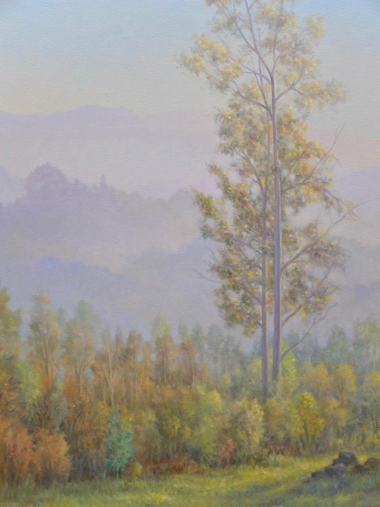 A lone eucalyptus tree stands tall in this vertical atmospheric landscape painting that features sunlit green grass, rolling purple hills and a hazy sky. A stunning work of original art by Willard Dixon, who is one of the finest American