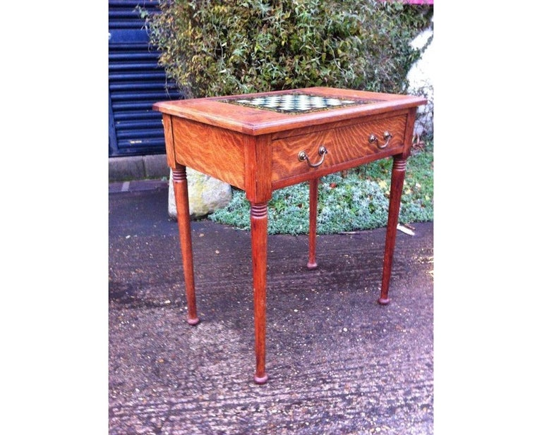 William Birch for Liberty & Co. A good quality Arts & Crafts oak chess table with hand painted glass to the underside of the chess playing board, with different marble effects and decorative floral boarders, a storage drawer below with the original