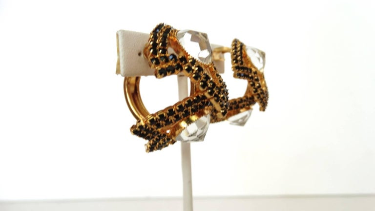 The classiest pair of black rhinestone hoops from prolific jewelry designer William De Lillo! Made of a brilliant gold metal and encrusted with black rhinestone gems in a leaf-like structure. Two large crystal gems at the either side of each