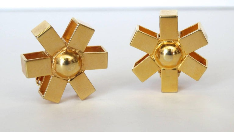 The chicest pair of gold asterisk clip on earrings from jewelry designer William De Lillo! Two asterisk style earrings cast from a brilliant gold metal, with a rounded dome in the middle. Clip on backs. Signed on each of the backs.