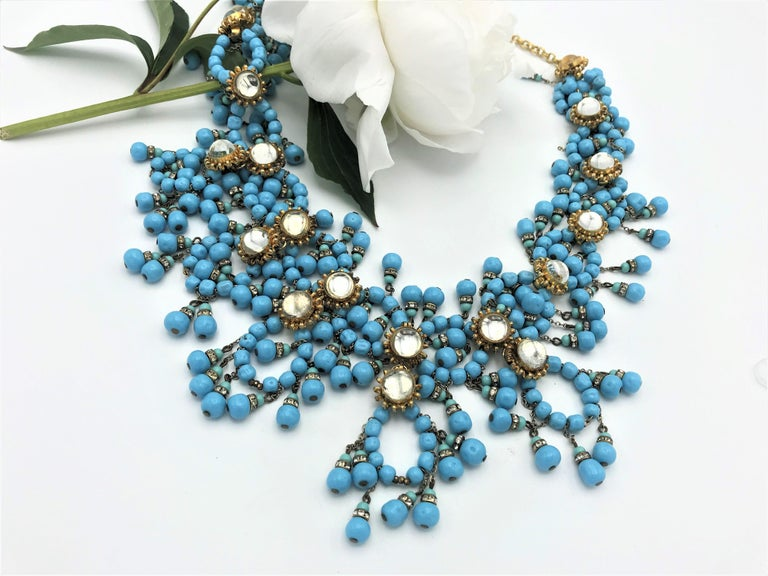 A beautiful imaginative necklace designed by William de Lillo. Consisting of many turquoise colored glass beads, different circles that are hung with many small turquoise tassels, as well as rosettes with round clear rhinestones connect the