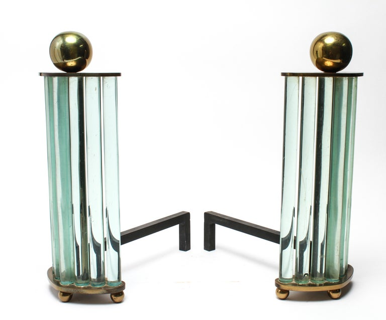Modernist pair of andirons made by the William H. Jackson Company in New York City. The pair has spherical brass finials atop rising glass rods mounted on a brass base. Maker's label on the underside. In great vintage condition with age-appropriate