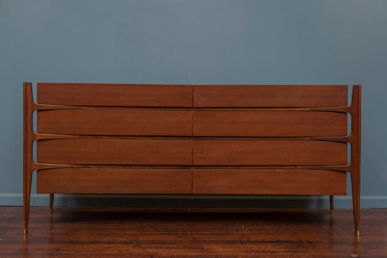 A spectacular circa 1950 sculptural eight-drawer dresser in walnut by William Hinn for Urban Furniture, and realized by Swedish Furniture Guild. Exposed biomorphic frame of exquisitely hand-sculpted solid walnut intersects and supports a beautifully