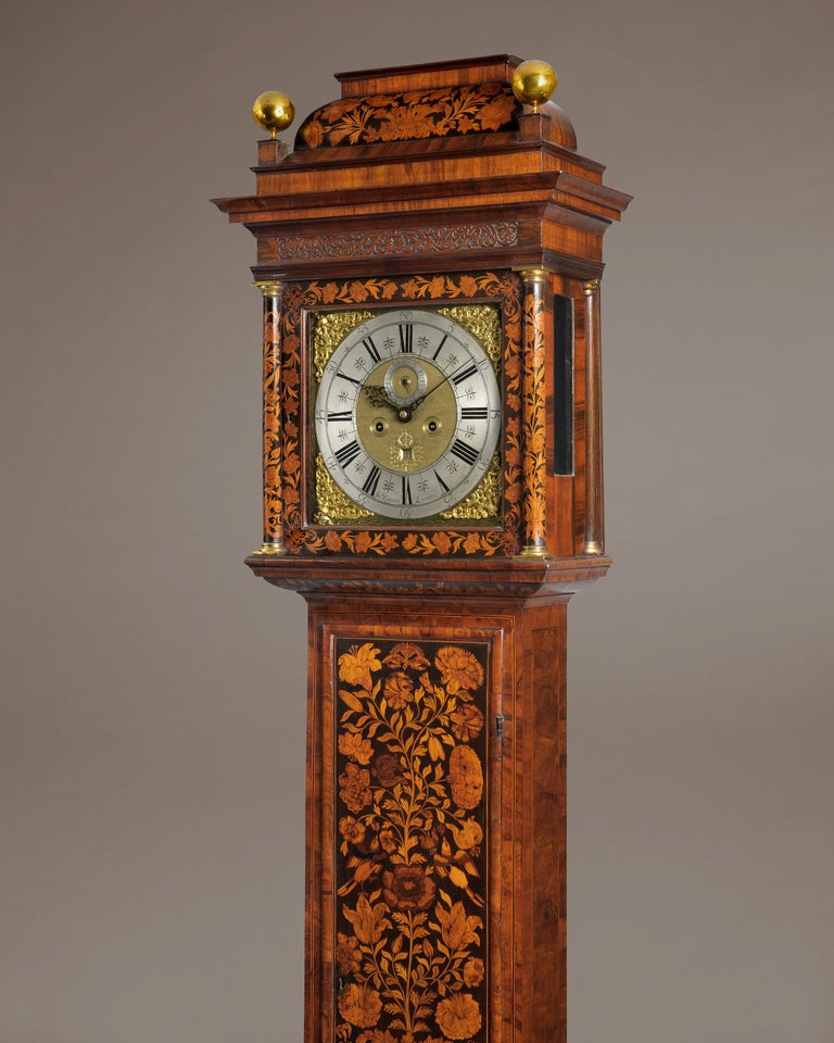 A fine William III period marquetry longcase clock of 8-day duration. The elegant slim caddy top case is veneered with walnut and decorated with colored scrolling flowers and foliage marquetry set against an ebony veneered background. The case