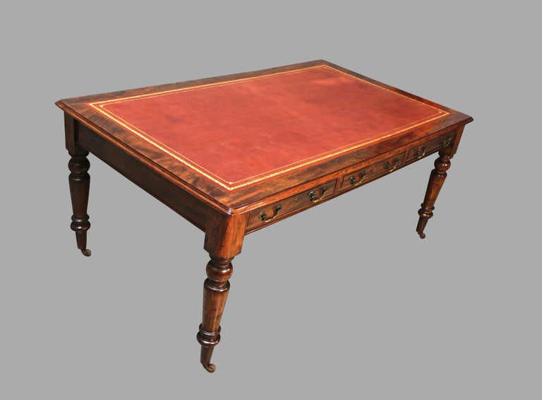 An English William IV or early Victorian period mahogany partners writing table, the brown gilt-tooled leather top above 3 drawers, the back identically configured, supported on turned legs ending in casters. Circa 1835-1850.