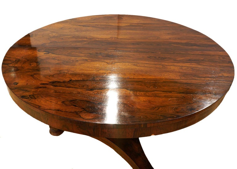 This good William IV rosewood pedestal center table or dining table features a round polished bookmatched figured top on a slightly tapering hexagonal pedestal on a triangular base resting on turned feet.