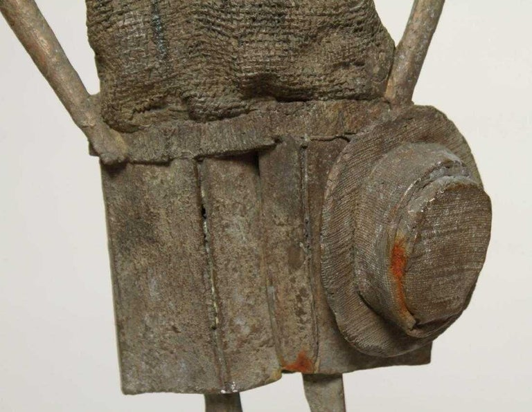 Mid-Century Modern wrought iron sculpture a person with oversize top, shorts, and carrying a hat, signed, artist's monogram and cipher, further mounted on a plaster base. 28