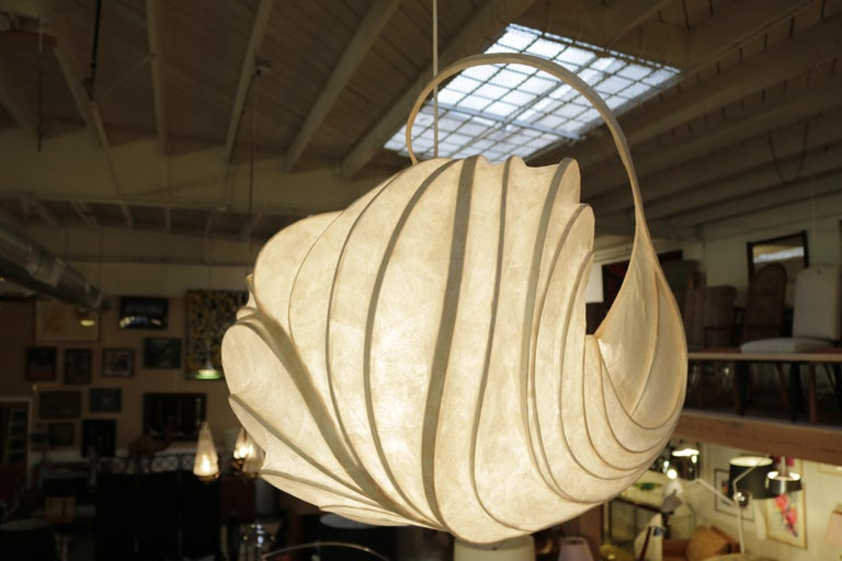 An original William Leslie 'light sculpture' in onion-like bulbous shape made from thin strips of wood bent into a frame then covered with paper soaked in polyvinyl resin and internally by incandescent light bulbs.