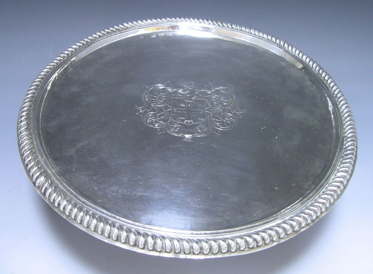 A distinctive William & Mary Antique Silver Tazza of plain circular form onto a cylindrical spreading foot. The surface of the tazza is embellished in the centre with, a contemporary coat of arms and has an impressive gadroon decorated border. The