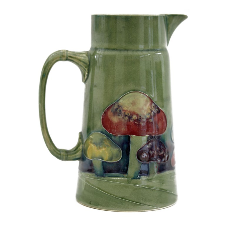 A rare William Moorcroft Claremont pattern jug of tall conical shape with a moulded handle and funnel shaped top with large pouring spout. The jug is hand decorated with tubelined mushrooms in streaked blue, red and yellow glazes on a green ground.