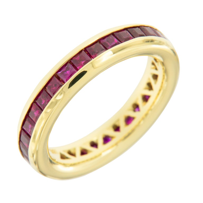 Expertly hand fabricated ring in royal 18 karat yellow gold with perfectly channel set 2.50 Cttw princess cut rubies by William Rosenberg. The classic color combination of fine red rubies & royal 18 karat yellow gold will always be a knockout! This