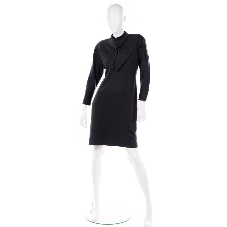 This timeless, 1970's vintage Travilla charcoal gray day dress feels like a wool blend with some stretch. The dress has a mock neck with built in scarf cutout detail. The sleeves are dolman style and there are shoulder pads to give this dress some