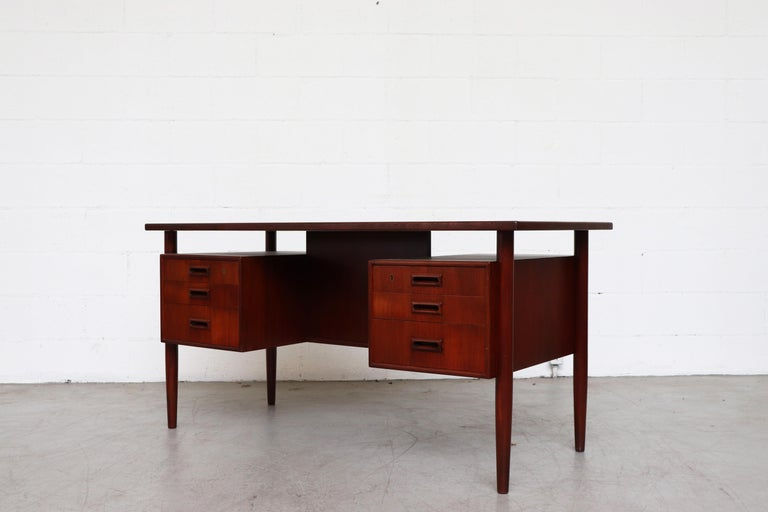 William Watting style teak desk with six drawers, floating top, and bookshelf cubbies on the back side. In original condition with some signs of wear consistent with its age and usage.