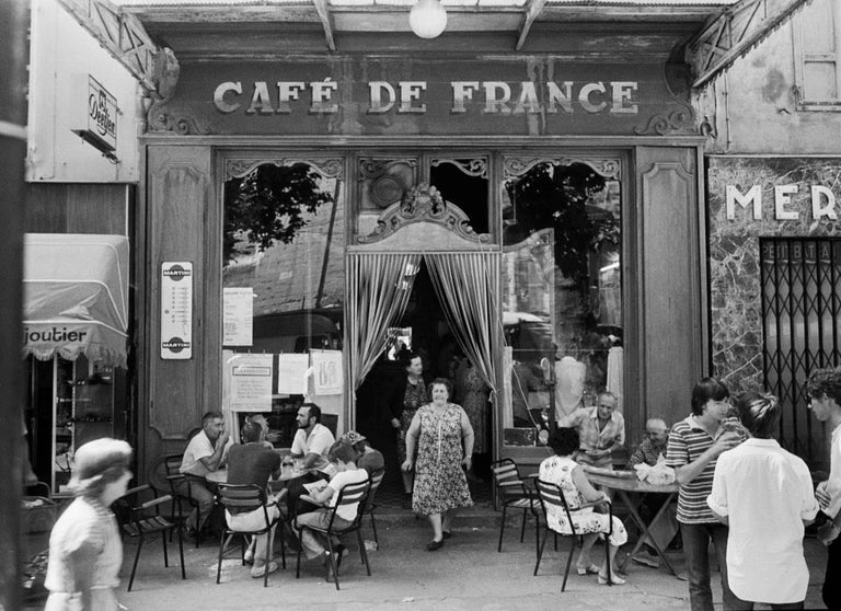 """Le Café de France à L'Isle-sur-la-Sorgue, 1979, by Willy Ronis is a gelatin silver later print, measuring 11.8"""" x 15.75"""". Signed recto, photographer's copyright stamp on verso, with printer stamp from 2001.  Interested in """"ordinary people with"""