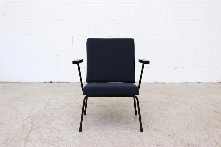 Black enameled steel frame with Bakelite armrests and new dense foam and newly upholstered with midnight navy fabric. Frame in original condition with wear consistent with it's age and usage. Others available and listed separately.