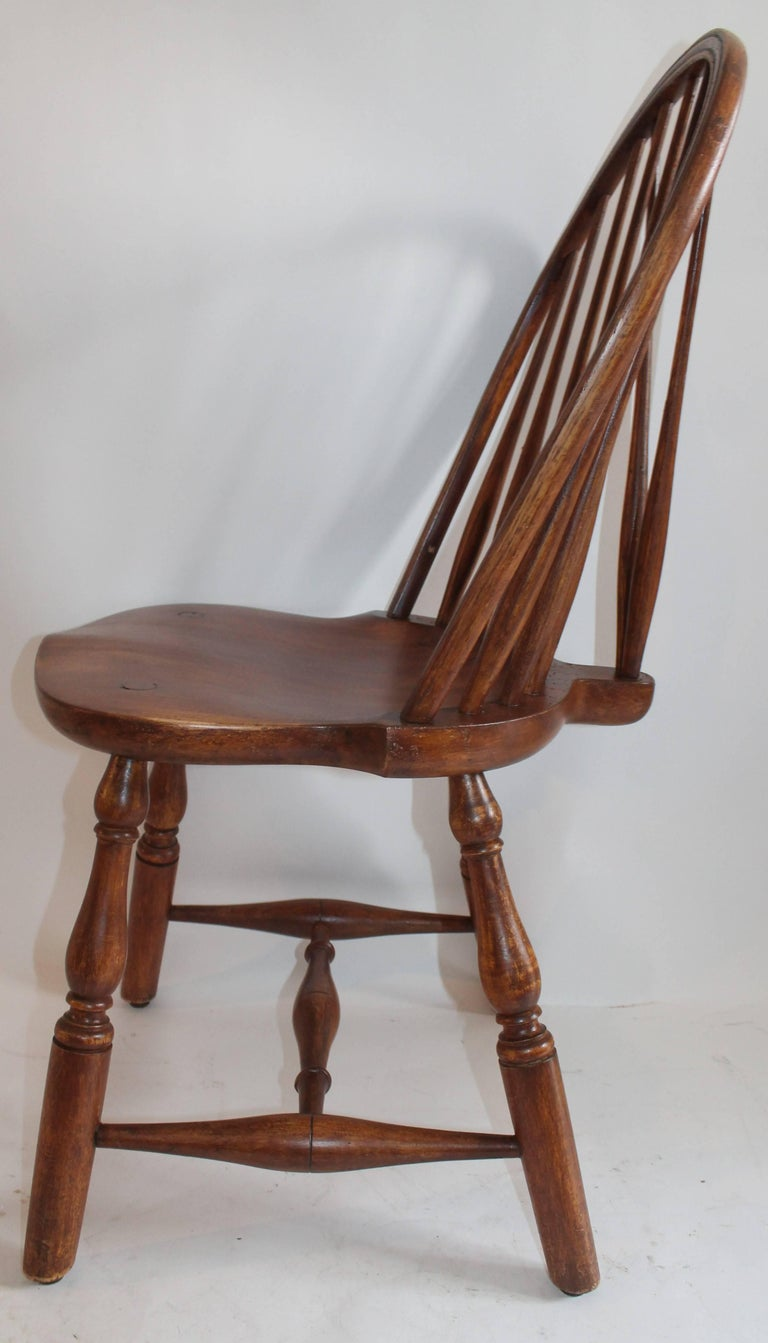 This fine example is a 20th century version of a 18th century brace back windsor chair. It is signed on the base The Marble & Shattuck Chair Co. The condition is very good and sturdy. This chair is made of maple.